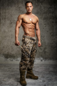 Man in army pants with naked torso. Vertical shoot